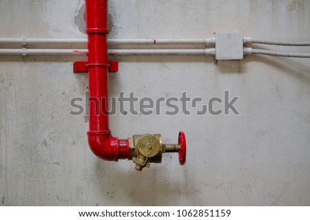 Red pipeline and red valve pipeline on concrete ceiling outside building.
