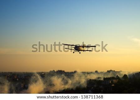 Red plane spraying mosquitoes over European town of Osijek, Croatia
