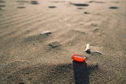 Red plastic bottle cork on sandy sea coast, polluted ecosystem,microplastics
