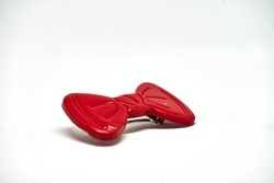 Red plastic bow on white background