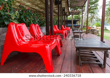 red plastic chairs on wood plank ground at restaurant terrace