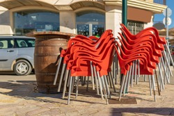 Red plastic chairs stacked outside a cafeteria closed by the Coronavirus crisis. Background of the image out of focus. Restrictions in the restoration by Covid-19