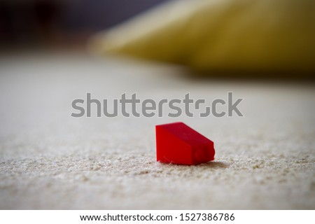 Red plastic childs building brick on a carpeted floor