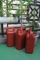 Red plastic jerrycan canisters in the small garden. As a garden decoration.