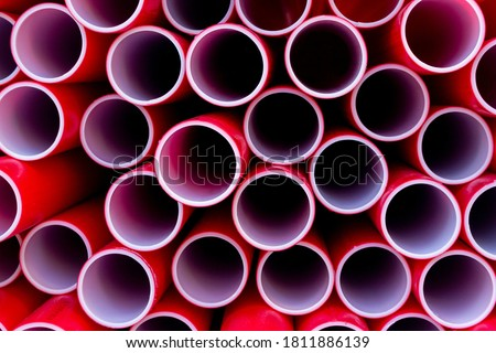 Red plastic pipes for building stacked on top of each other. The colors and patterns of PVC pipes for the background. Plastic Pipes For Pipelines and optical cables