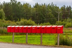 Red plastic post boxes near the road on the forest background. Domestic countryside landscape, Kainuu region in Finland