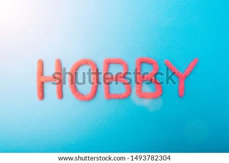 Red plasticine hobby lettering on blue background, hobbies concept, inscription #1493782304