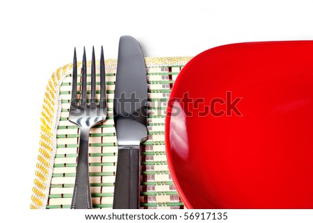 Red plate, knife and fork isolated on white background