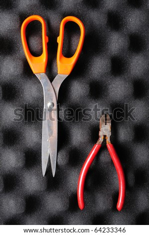 red pliers with rust and dirty orange scissors on black wave sponge
