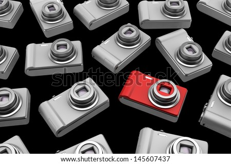 red point and shoot photo camera among gray similar isolated on black background