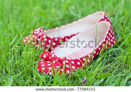Red polka-dot shoes in a green grass