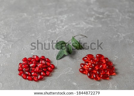 red pomegranate berries with leaves and vitamins in capsules on a rough gray background Concept of healthy nutrition, vitamins and nutritional supplements Photo stock ©