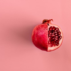 Red pomegranate fruit on pastel pink background. Minimal flat lay concept.