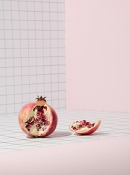 Red pomegranate on a checkered pink background. Concept template food blog, social media, diet concept. Conceptual minimalistic photography of fruit. Copy space