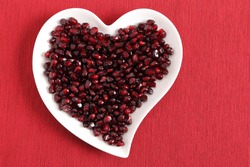 Red pomegranate seeds on a white heart-shaped plate.
