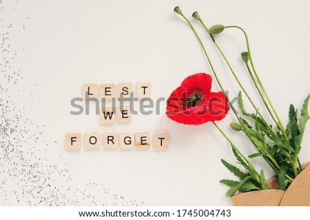 Red poppy flowers in envelope on white background. Wooden alphabet text Lest we forget. Remembrance day, Veterans day, Anzac day, lest we forget, Memorial Day concept