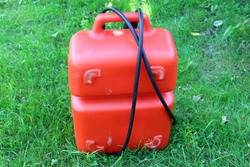 Red portable plastic fuel tank 24-25 liters with handle and tube for outboard motor in summer on green grass - motor boat trip