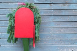 Red post box decorated with green fir branches. Attached to wall from brown wooden planks. Drop box american type. Concept of Christmas, New Year's holiday.