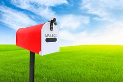 Red post mailbox with blured outdoor green lawn grass and blue sky on background.