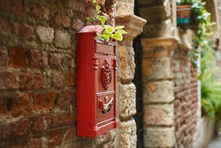 Red postbox on an antique brick wall