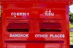 Red postbox with slots marked in Thai, and English for