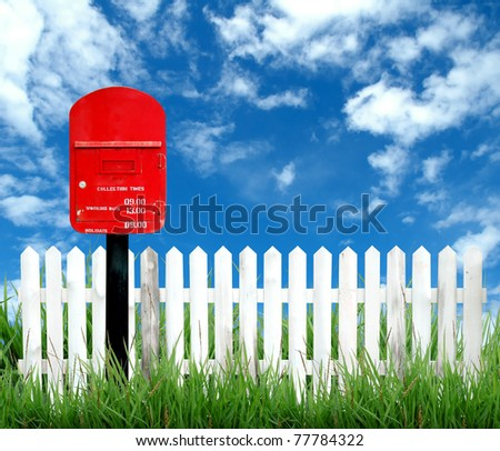 red postbox with white fence and blue sky
