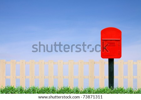 red postbox with white fence and clear blue sky