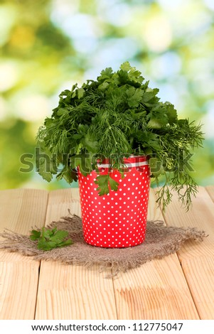 Red pot with parsley and dill on wooden table on natural background