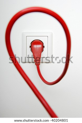 Red power cable plugged in electric outlet, on white background