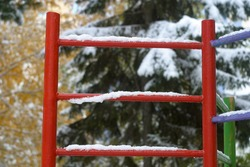 Red, purple ladder stair in the playground, covered with white snow, fallen yellow leaves, green needles. The first snow in autumn, in October. Autumn and winter background