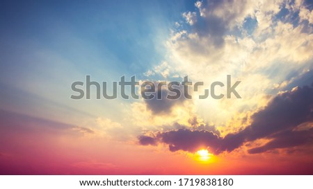 red purple with orange sunset in overcast blue sky with sun rays light ストックフォト ©