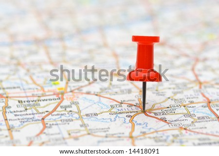 Red push-pin marking a location on a road map, selective focus