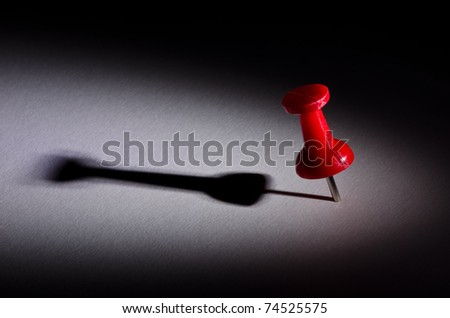 Red push pin under a spotlight with long shadow casted