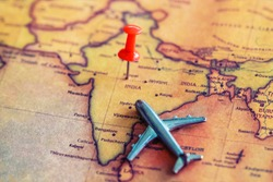 Red pushpin and mini airplane on India part of world map. Travel to India concept. Selective focus.