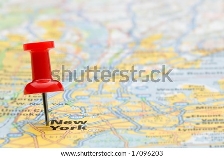 Red pushpin marking the location of New York City on a road map, selective focus
