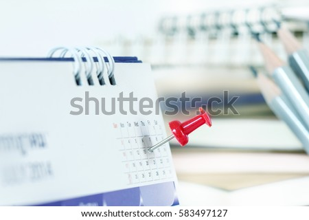 Red pushpin on calendar page for remind and marked important events #583497127