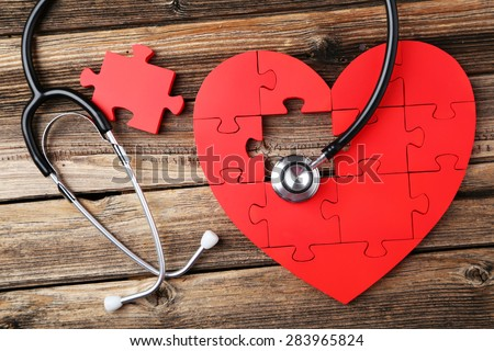 Red puzzle heart with stethoscope on brown wooden background #283965824