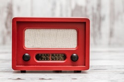 Red radio with retro look on white wooden background
