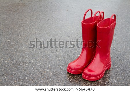Red rain boots on wet pavement, room for copy space