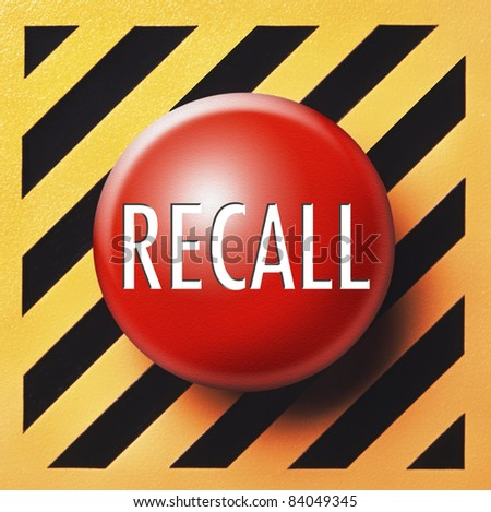 Red recall button with white lettering on a yellow and black background - stock photo