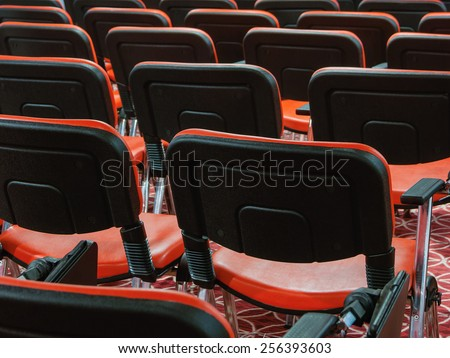 red recliners stand rows in an empty conference hall