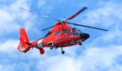 Red rescue helicopter moving in blue sky with blur propeller