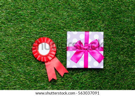 Red reward and gift box on green grass background, above point of view #563037091