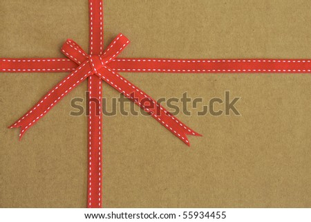 Red ribbon and bow on recycled card as background