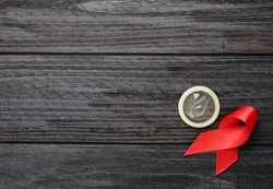 Red ribbon and condom on black wooden background, flat lay with space for text. AIDS disease awareness