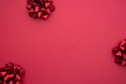 Red ribbon bows over red background, flat lay. Party, birthday, Christmas or Valentine's Day mock up. Flat lay.