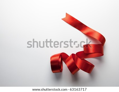 Red ribbon nicely uncurled on white background with natural lighting.  Preparation for gift wrapping.