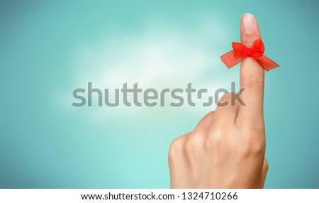 Red ribon on finger