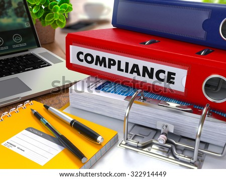 Red Ring Binder with Inscription Compliance on Background of Working Table with Office Supplies, Laptop, Reports. Toned Illustration. Business Concept on Blurred Background.