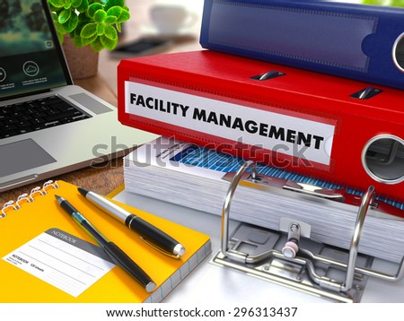 Red Ring Binder with Inscription Facility Management on Background of Working Table with Office Supplies, Laptop, Reports. Toned Illustration. Business Concept on Blurred Background.